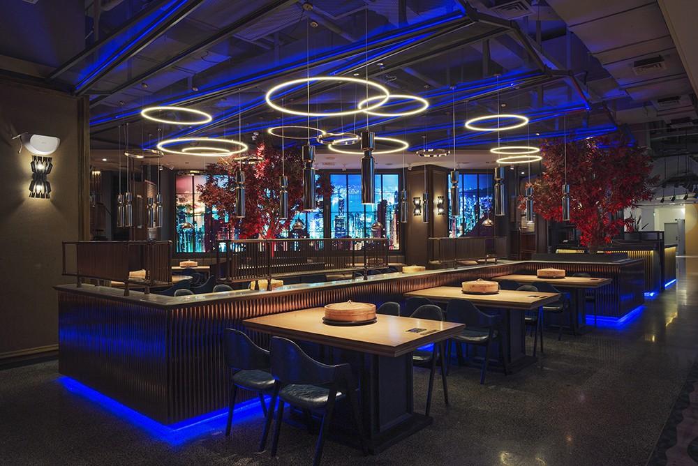 天花板采用宝蓝色的线条感灯光搭配荧光色的光圈,营造出一种光怪陆离的空间氛围,背景墙选用灯光璀璨的都市夜景,使设计师所要表达的繁华感呼之欲出。
