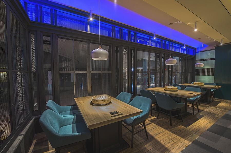用餐区采用两种不同明度的蓝色,搭配棕黄色的原木餐桌,并用象牙白色的吊灯加以点缀,轻松而又惬意。