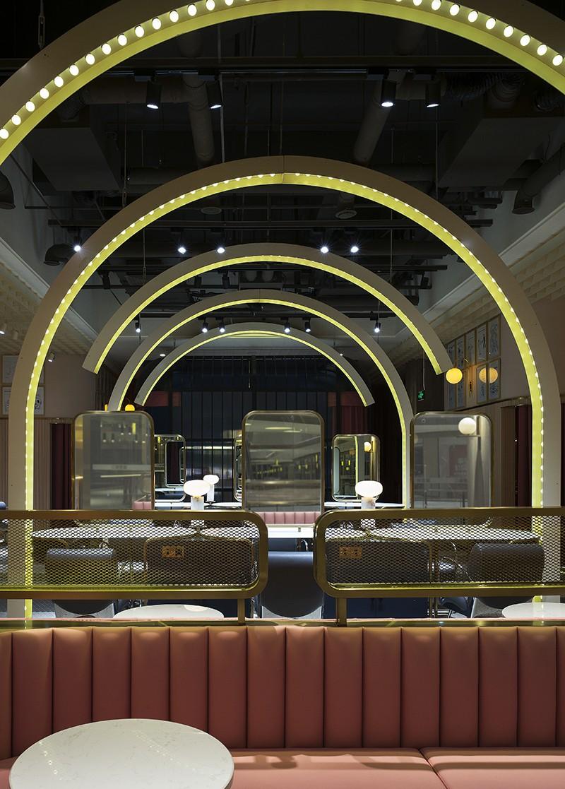 灯光往往是美发店装饰中最重要的手段之一,而整个美发店的服务区域集中在了大厅中央,为了避免敞开式空间的过分空旷,设计师通过选用连排的拱形吊灯以层层递进的视觉效果,将这一区域进行了集中表现。